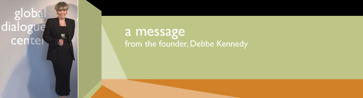 a banner with the words, a message from the founder, Debbe Kennedy with her photo standing in the lobby of the Global Dialogue Center